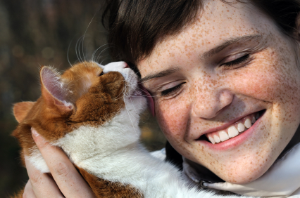 happy freckled girl and funny red cat