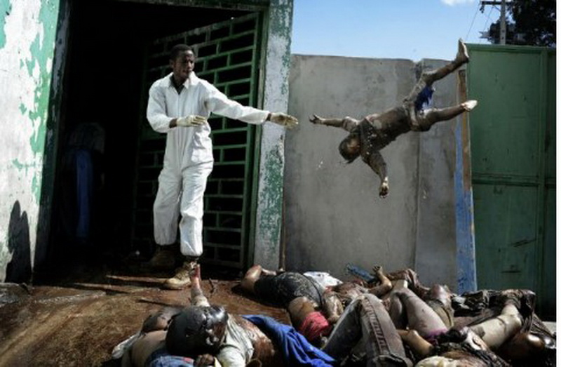 man throwing a dead child into a makeshift Morgue in Haiti on Jan 15, 2010.